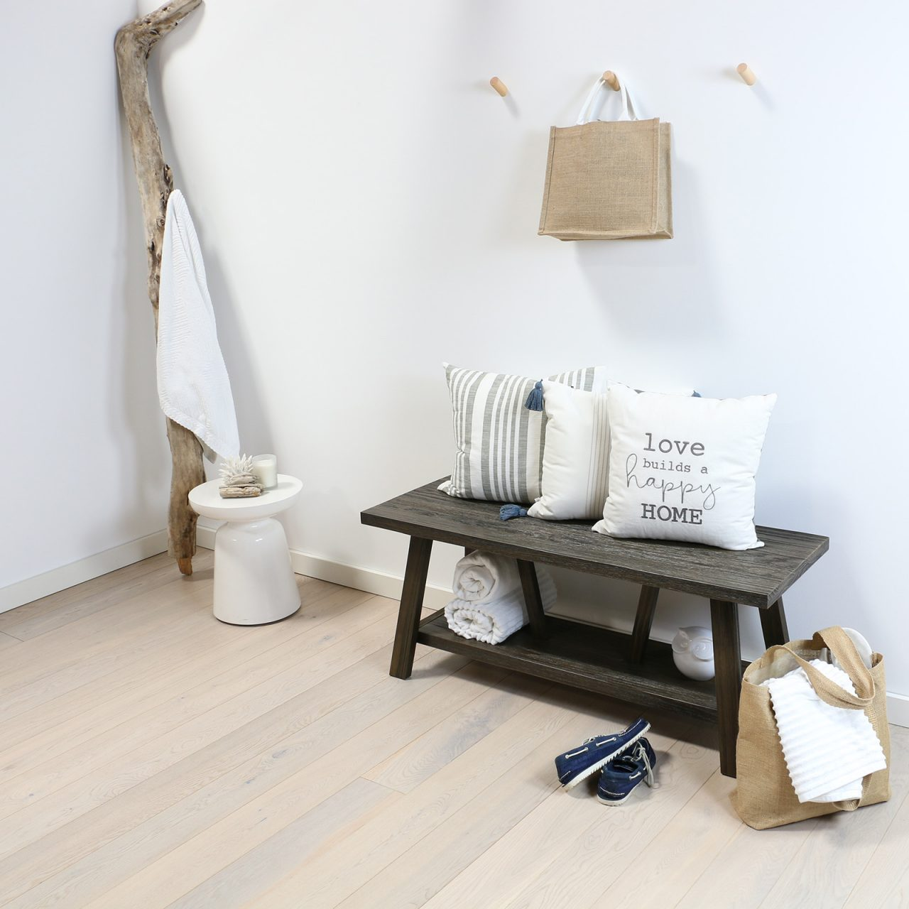 Coastal entry with wood bench and engineered hardwood flooring in white tones